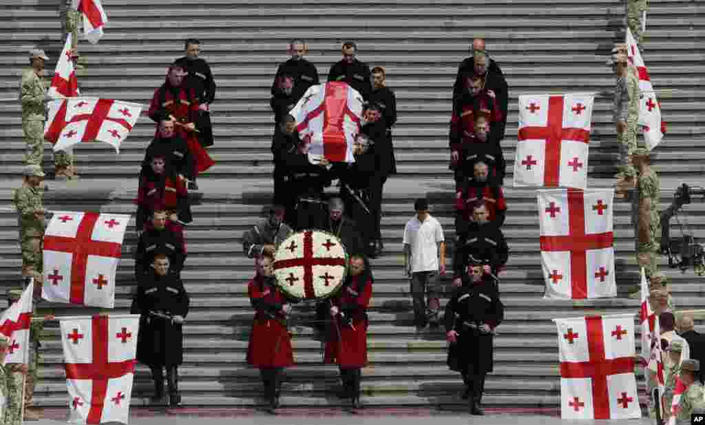 Georgian honor guards carry the coffin of the deceased former President Eduard Shevardnadze, covered by National flag, from the Holy Trinity Cathedral during his funeral service in Tbilisi. The late president,86, has been buried next to his wife in the the Krtsanisi Presidential Residence of Tbilisi.