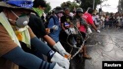 Para demonstran anti-pemerintah memotong kawat berduri barikade polisi dekat gedung pemerintahan di Bangkok (25/11).