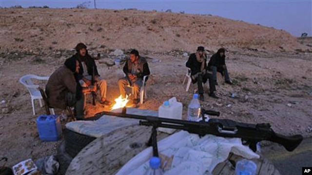 Libyan anti-government fighters sit by a fire to stay warm as they control a checkpoint on the outskirts of the southwestern town of Nalut, Libya, February 28, 2011