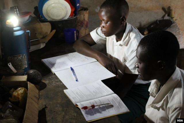 Michael Mugerwa's students come to his house to study using his solar light, Kiwumu, Uganda, Feb. 28, 2014. (Hilary Heuler/VOA)