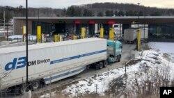 Truk dari Canada menunggu saat akan melintasi perbatasan menuju Amerika Serikat di Derby Line Vt, 18 Maret 2020. AS akan membuka kembali perbatasan ini bulan November mendatang, setelah ditutup akibat pandemi COVID-19. (AP Photo/Wilson Ring).