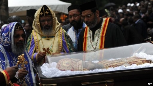 Priests conduct ceremony next to casket bearing remains of Patriarch of the Ethiopian Orthodox Church, Abune Paulos, Aug. 23, 2012.