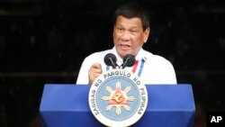 FILE - Philippine President Rodrigo Duterte gestures while addressing the crowd at the 120th Philippine Independence Day celebration, June 12, 2018. Duterte pressed congress to pass the Bangsamoro Organic Law.