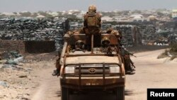 Kenya Defense Force (KDF) soldiers, serving in the African Union Mission in Somalia (AMISOM), patrol past stockpiles of charcoal near the Kismayo sea port town in lower Juba region, Somalia, Feb. 27, 2013.