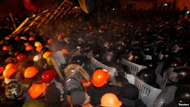 Pro-European integration protesters attempt to push back riot police at Independence Square in Kyiv December 11, 2013.
