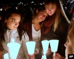 Umpqua Community College students Nicole Zamarripa, left, Kristen Sterner, center and Carrissa Welding, right, join others at Stewart Park, in Roseburg, Ore., for a candlelight vigil for those killed during a fatal shooting at the school, Oct. 1, 2015.