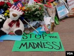 "Among the tributes honoring Dallas shooting victim outside Dallas police headquarters, a sign urges the country to ""Stop the madness,"" July 11, 2016. (M. O'Sullivan/VOA)"