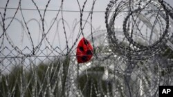 FILE - A punctured ball hangs on barbed wire in the heavily guarded camp at Serbia's border with Hungary, near the Horgos border crossing, Serbia, Sept. 19, 2017.
