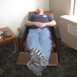 John Davis sleeping in a chair that reclines into bed while his wife is in the ICU.