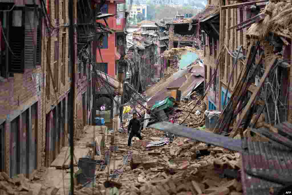 A man walks through rubble of houses damaged by the earthquake in Bhaktapur near Kathmandu, Nepal. Hungry and desperate villagers rushed towards relief helicopters in remote areas Tuesday, begging to be airlifted to safety, four days after a monster earthquake killed nearly 4,500 people.
