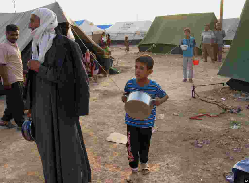 Iraqis who fled from Baqouba and other towns after advances by Islamic militants wait for food distribution at a camp in Khanaqin, northeast of Baghdad, July 6, 2014.