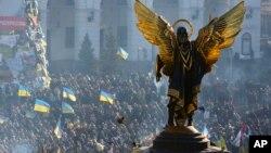 """Para aktivis pro-Uni Eropa terlihat berada di sekitar patung """"The Archangel Michael"""" dalam aksi protes di lapangan Kemerdekaan di Kiev, Ukraina (14/12)."""