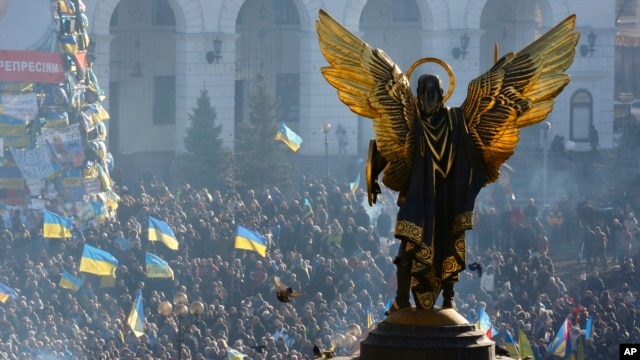 The Archangel Michael statue towers over pro-European Union activists during a rally in Independence Square in Kyiv, Ukraine, Saturday, Dec. 14, 2013.