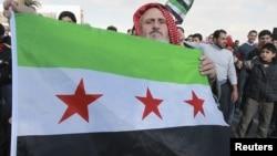 居住在約旦的一示威者12月14日在安曼的敘利亞使館前高舉反對阿薩德的旗幟