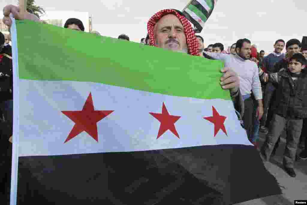 A Syrian protester living in Jordan holds up a Syrian opposition flag during a protest against Syria's President Bashar al-Assad, outside the Syrian embassy in Amman December 14, 2012. REUTERS/Muhammad Hamed (JORDAN - Tags: POLITICS CIVIL UNREST)