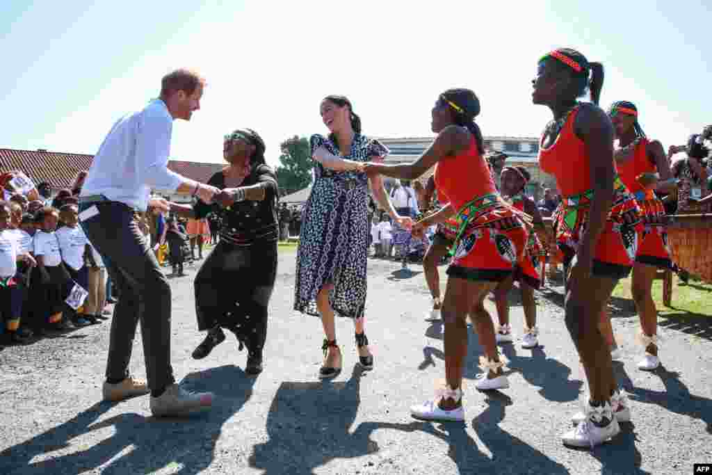 "Prince Harry, Duke of Sussex and Meghan, Duchess of Sussex, dance during a visit to the ""Justice Desk,"" an NGO in the township of Nyanga in Cape Town, as they begin their tour of the region."
