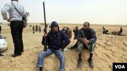 Seorang tentara pemberontak (kiri) mengusung senapan di pinggiran kota Ajdabiya, di rute menuju Brega, Rabu (2/3).