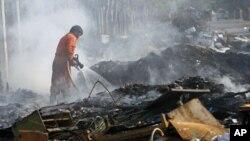泰國遭受50年來最嚴重的水災已經退去,1月6號,一名消防員正在撲滅廢墟上的火。