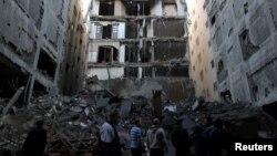 Warga Palestina memeriksa bangunan yang hancur akibat serangan udara Israel di Jalur Gaza, Selasa (13/11).