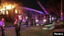 Bomberos intentan apagar un incendio en un edificio abandonado en San Luis, Missouri luego de las protestas por la muerte de un adolescente negro.