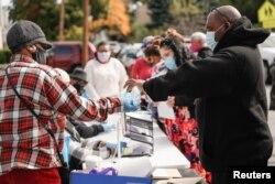 Relawan membagikan masker sebagai bagian dari program penjangkauan kepada komunitas kulit hitam untuk meningkatkan partisipasi uji coba vaksin di Rochester, New York, AS, 17 Oktober 2020. (Foto: Reuters)