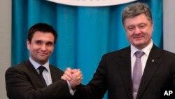 Ukrainian President Petro Poroshenko (R) congratulates new Ukrainian Foreign Minister Pavel Klimkin in Kyiv, June 19, 2014.