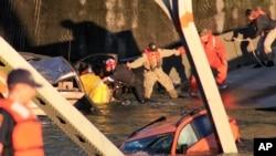 Regu penyelamat membentuk rantai manusia untuk memindahkan seorang perempuan yang menjadi korban rubuhnya jembatan I-5, yang menghubungkan negara bagian Washington dengan Kanada (23/5). Sebagian kendaraan yang melintas di atas jembatan tersebut jatuh ke sungai Skagit. Dilaporkan tidak ada korban jiwa dalam insiden tersebut.