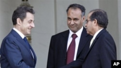 French President Nicolas Sarkozy, left, shakes hands with Mahmoud Jibril, right, and Ali Al-Esawi, representatives of the newly formed council based in the eastern Libyan city of Benghazi, after a meeting at the Elysee Palace, in Paris, March 10, 2011