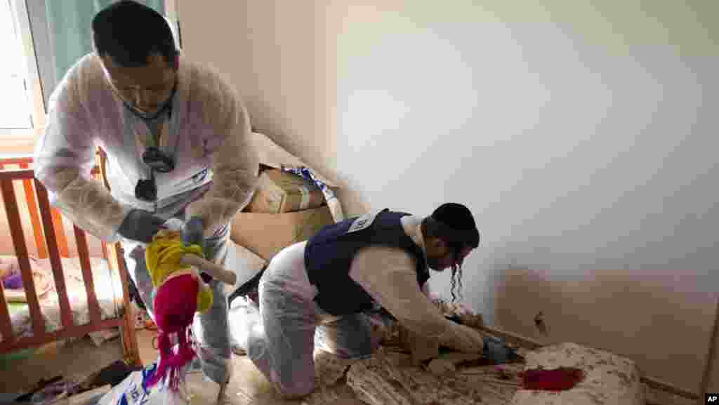 Sukarelawan Zaka membersihkan noda darah di apartemen yang terkena roket di Kiryat Malachi.