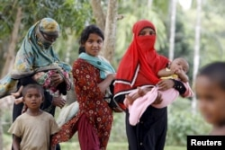 Rohingya women and children walk back from a hospital near the Kutupalong refugee camp, Bangladesh, May 31, 2015.