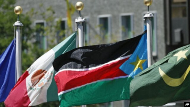 The flag of South Sudan (C) flies after the United Nations General Assembly voted on South Sudan's membership to the United Nations at UN headquarters in New York, July 14, 2011