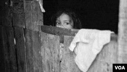 Karen María Hernández de 5 años observa como niños juegan en su barrio a las afueras de Tegucigalpa, Honduras.