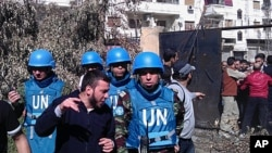 A handout picture released by the Syrian opposition's Shaam News Network shows Syrian residents talking to Moroccan UN observer, Colonel Ahmed Himmiche (R) during the monitors' visit to the Khalidiya district in the restive city of Homs, April 21, 2012.