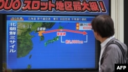یک شهروند کره جنوبی مقابل تلویزیونی که مسیر موشک جدیدا آزمایش شده کره شمالی را نشان می دهد.