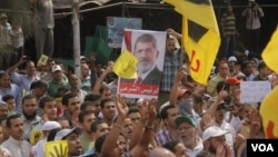 Protesters at a Muslim Brotherhood organized rally hold up a poster of ousted president Mohamed Morsi in Cairo, Sept. 27, 2013. (H. Elrasam for VOA)