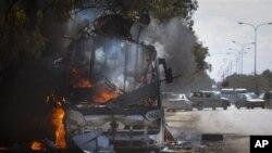 Un autobus en feu sur une route menant à Benghazi.