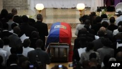 People attend a family ceremony for former Haitian dictator Jean-Claude Duvalier at the chapel of the school Saint-Louis Gonzague in Port-au-Prince, Oct. 11, 2014.