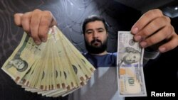 FILE - A money changer displays a U.S. $100 bill and the amount being given when converting it into Iranian rials at a currency exchange shop in Tehran's business district, Jan. 20, 2016. The rial hit record lows against the dollar in June 2018.