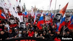 People march behind a banner to commemorate Kremlin critic Boris Nemtsov, who was shot dead Friday, in Moscow, Russia, March 1, 2015.