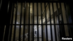 A guard stands behind bars at the Adjustment Center during a media tour of California's Death Row at San Quentin State Prison in San Quentin, California Dec. 29, 2015.