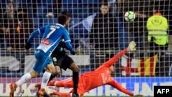 L'attaquant espagnol de l'Espanyol Gerard Moreno, à gauche, décoche un tir et marque lors du match de la Liga contre le CF Real Madrid au stade RCDE de Cornella de Llobregat, le 27 février 2018.