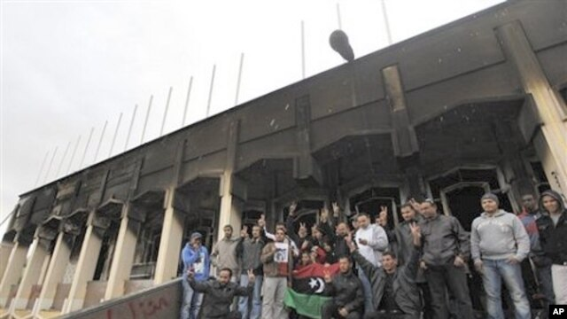 Libyan youth gather for a souvenir picture at the entrance to the burned house of Libyan Leader Moammar Ghadafi inside Al-Katiba military base, in Benghazi, Libya, February 27, 2011