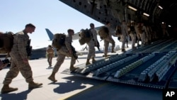 FILE - U.S. Marines are seen boarding a military transport plane.