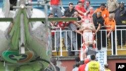 Un aficionado herido es cargado en camilla durante una batalla campal de aficionados del fútbol.