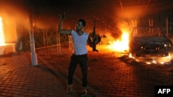 A protester waves his rifle as flames engulf the U.S. Consulate compound in Benghazi September 11, 2012.