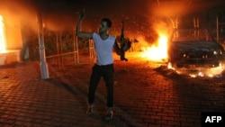 Seorang pria bersenjata berada di komplek konsulat AS di Benghazi, Libya yang terbakar akibat serangan para demonstran yang marah atas film yang dinilai menghina Nabi Muhammad (11/9).