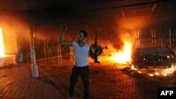 An armed man waves his rifle as buildings and cars are engulfed in flames after being set on fire inside the U.S. consulate compound in Benghazi late on September 11, 2012.