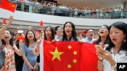 親北京的支持者手舉中國國旗在香港金融中心商場唱中國國歌。 (2019年9月12日)
