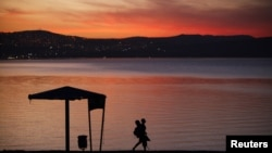 FILE - A man walks on the shore of the Sea of Galilee during sunset near the northern city of Tiberias.