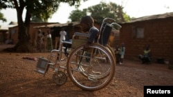 Giovanni Mougounou, 10, who lost both legs in April 2013 to what his family say was a rocket-propelled grenade launched by Seleka fighters on a church, pushes his wheel chair in the Boy Rabe district of Bangui, Central African Republic, February 4, 2014.